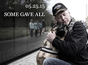 Veteran hugging his dog at the Vietnam War Memorial Wall with text Some Gave it All 5-25-15.