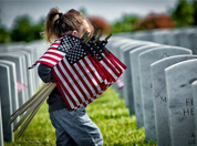 A little girl carrying flags at the Sacramento Valley National Cemetery