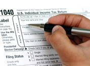 A hand filling out an IRS tax form