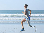 Man with a prosthetic leg running on the beach.