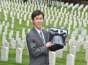 Picture of a man holding a photo in a cemetery