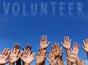 raised hands below skywriting 'Volunteer'