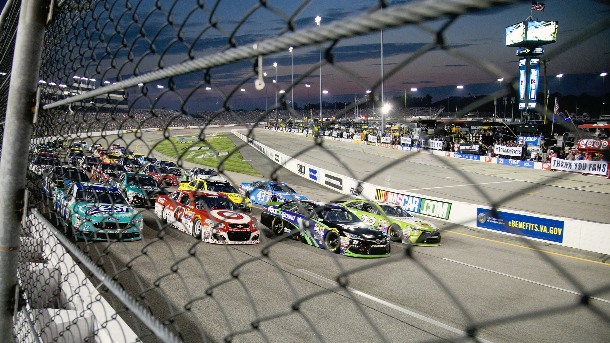 A tight pack of cars race on the Richmond International Raceway at a qualifying event