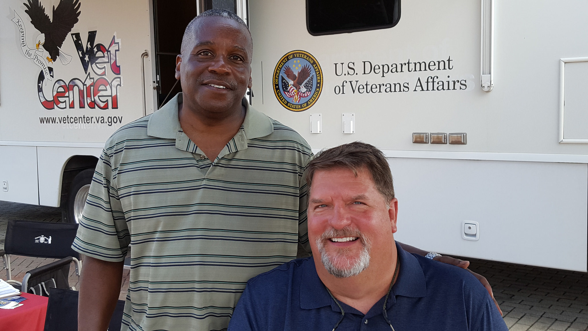 VA health expert poses with Veteran in front of a Mobile Vet Center