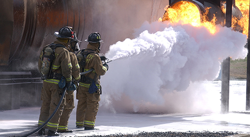 Three firefighters during a training exercise.