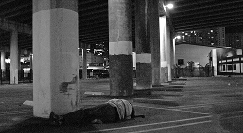 Homeless person sleeping in Miami parking garage.