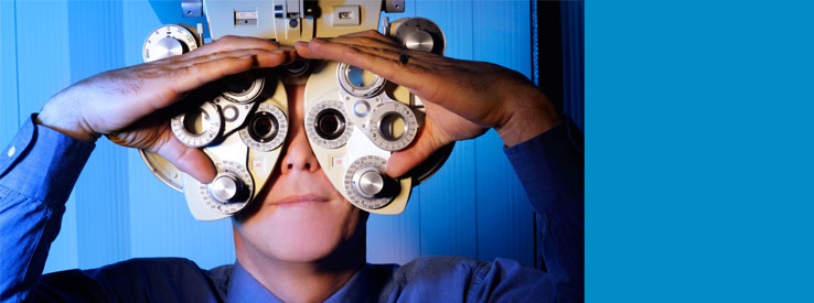 Man looking through ophthalmology machine