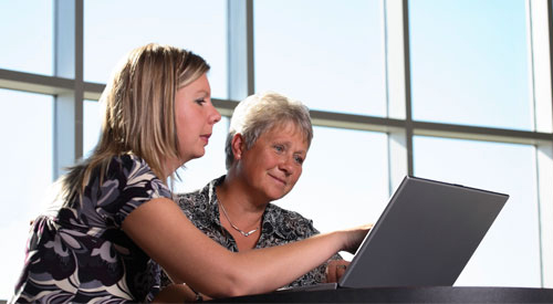 woman helping another on the computer