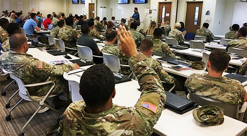 Service member raising his hand during class