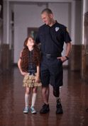 picture of policeman with prosthetic leg assisting a girl