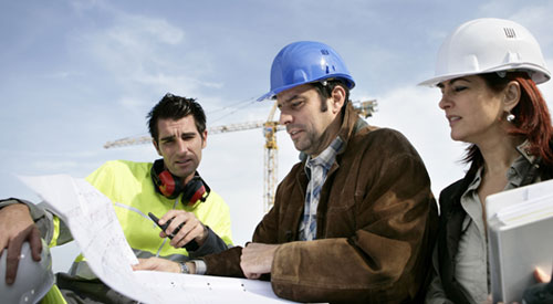architect and construction workers reviewing drawings